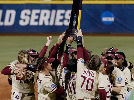 Florida State players celebrate with the trophy after defeating Washington 8-3 in the second game of the best-of-three championship series in the NCAA softball Women's College World Series in Oklahoma City, Tuesday, June 5, 2018. Florida State won the title.