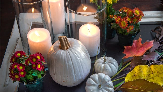 Create a coffee table vignette with candles, glass pillars, painted pumpkins, mums and fall foliage.