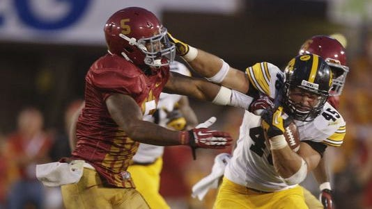 Iowa running back Mark Weisman stiff-arms Iowa State defensive back Jacques Washington during an NCAA college football game between the University of Iowa and Iowa State on Saturday, Sept. 15, 2013, at Jack Trice Stadium in Ames, Iowa.