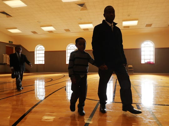 Joseph Genda walks with his sons Norman, 10, and Patrick, 4, at church in Salt Lake City on Sunday, Nov. 18, 2018.
