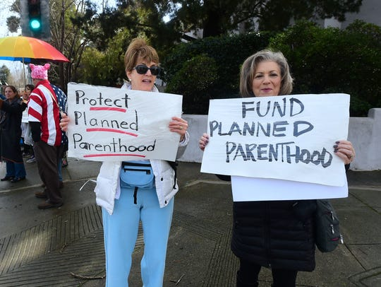 Esther Harris (L) and Rosalie Emanuel (R) hold placards