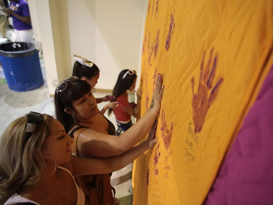 Tanya Garcia, Indio, front, and Serena Salas, Coachella, put their hand prints on a quilt during a fundraiser for Desirae Cechin who has stage IV high-risk neuroblastoma, which affects the nervous system. So far, $200,000 of the $300,000 has been raised for her treatment. Photo taken on Saturday, at the Riverside County Fairgrounds in Indio.