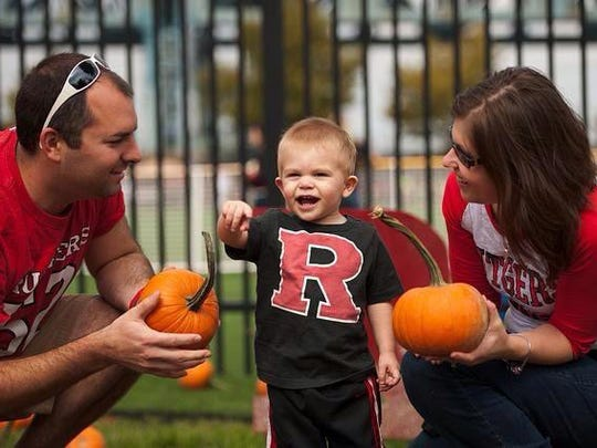 Rutgers-Camden graduates Scott and Jennie Owens with their son in pint-sized Rutgers gear.