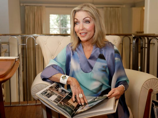 "Interior designer Jan Showers holds her book ""Glamorous Retreats,"" at her home in Dallas. Showers encourages people to take the time to design their own retreat, be it a vacation spot or just a special place at home."