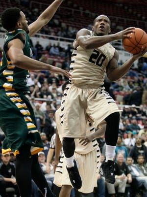 Oakland's Kay Felder (20) goes to the basket against Wright State's Mark Alstork (23) during the second half of Oakland's 59-55 loss in the Horizon League tournament semifinal Monday at Joe Louis Arena.