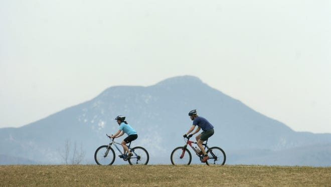 Mountain bikers are flanked by Camels Hump mountain at Catamount Family Outdoor Center in Williston. Photographed April 12, 2006.