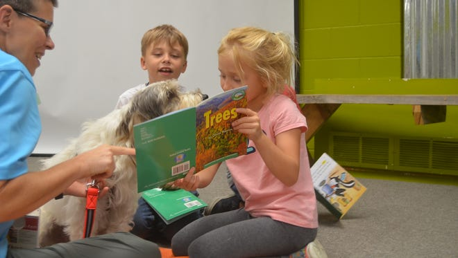 """Six-year-old Vanessa Halverson shows her """"Trees"""" book to Sprocket during the Hendersonville's SMORE Reading Camp July 2, 2018."""