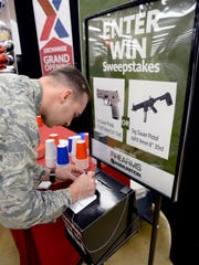 Capt. Hawkins Thomas, Air Force Reserve Officer Training Corps field trainer, completes an entry form during the grand opening of the firearms counter at the Maxwell Base Exchange on Feb. 17.
