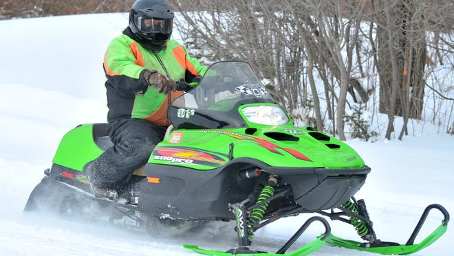 A snowmobiler cruises on a trail Saturday, Feb. 1, 2014, Nine Mile County Forest Recreation Area in Rib Mountain.