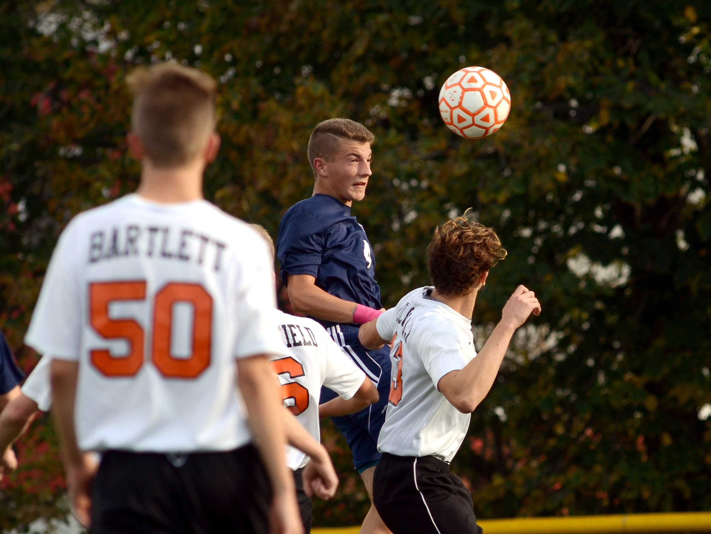 Blue Devils' Brandon Kunce heads the ball Monday, Oct. 12 during high school soccer action at Almont.