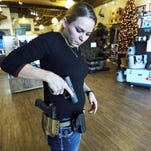 Alexandra Wilson, marketing director and firearms instructor at Sportsman's Elite indoor shooting range and pro shop at 4520 Doniphan, shows two varieties of hand gun holsters. The new open carry law is now in effect in Texas.