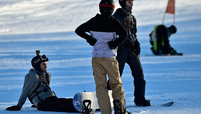 Snowboarders relax after a ride down the slopes during opening day at Whitetail Resort. The ski lodge opened with all machine-made snow.