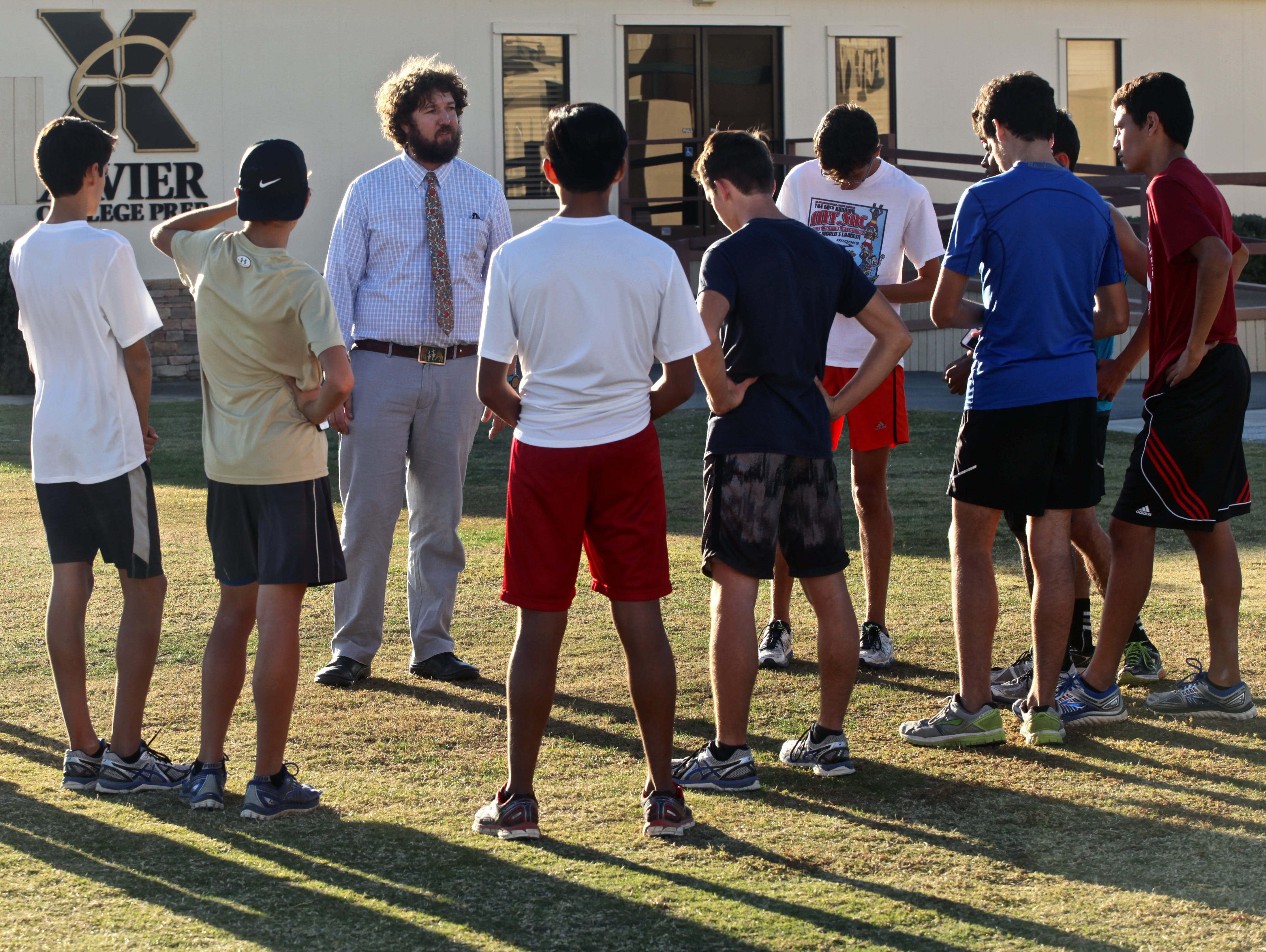 Xavier Prep cross country head coach Aron Lyons talks to students about the importance of discipline during a practice session on Tuesday, Nov. 24, 2015.