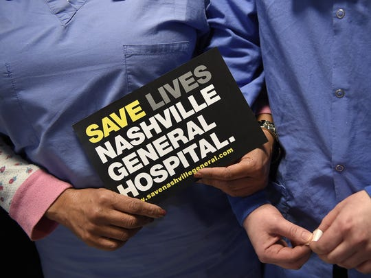 Staff members hold signs at a news conference Jan. 26, 2018, at Nashville General Hospital in response to the announcement of a proposed $13.2 million subsidy for the hospital.