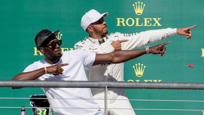 Lewis Hamilton, right, poses with Olympic champion Usain Bolt after Hamilton won the United States Grand Prix Sunday at Circuit of the Americas.