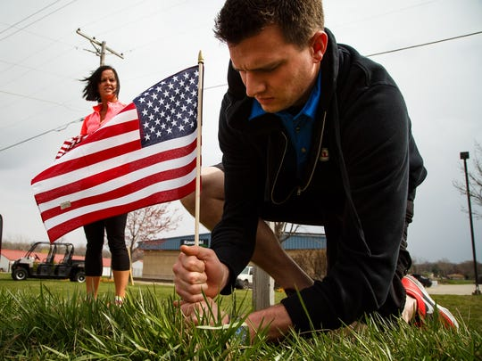Ryan Printy of Grimes places a flag along NW 2nd street in Des Moines on Wednesday, March 30, 2016 with the help of Mollie Lundstrom of Ankeny. They placed 26 flags before running out in honor of Officer Susan Farrell whose funeral procession will be passing by.