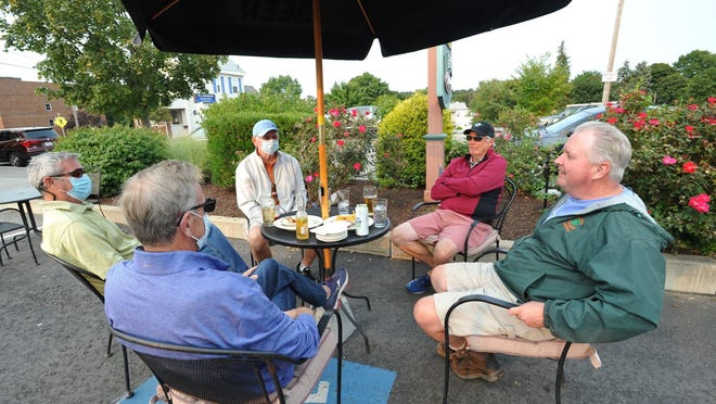 Enjoying appetizers and drinks at the Darcy's Pub patio are clockwise from center foreground, Bill Hurley of Milton, Jerry McEleney of Canton, Dick Burke of Milton, John Monahan of Milton, and Tom Huffan of Norwood at the Common Market restaurant on Willard Street in Quincy, Tuesday, Sept. 15, 2020. Tom Gorman/For The Patriot Ledger