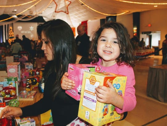 In this 2016 file photo, a young child clings to her toys she selected at the 2016 Otero County Toys for Tots program at the Sgt. Willie Estrada Civic Center.