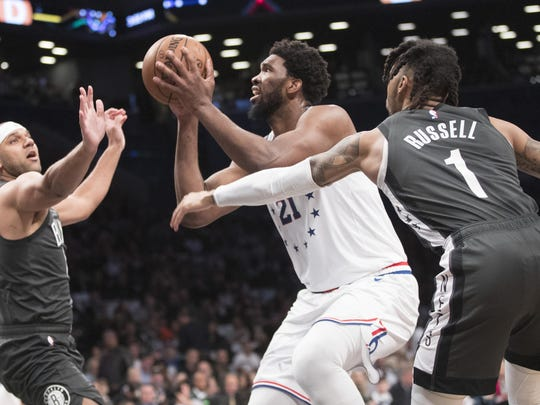Philadelphia 76ers center Joel Embiid (21) goes to the basket against Brooklyn Nets guard D'Angelo Russell (1)and forward Jared Dudley during the first half of Game 4 Saturday.
