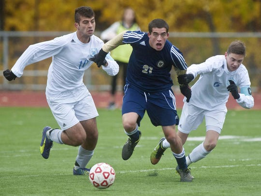 South Burlington's Ismail Temerov (left) and Alex Pasanen chase after Essex's Noah Ferris during 2014 Division I boys soccer final.