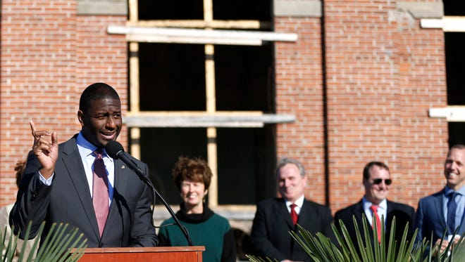 """Mayor Andrew Gillum talks about The Edison before its opening during the groundbreaking ceremony for the space on Thursday Feb. 5, 2015. """"We have historic preservation being kept alive,"""" said Mayor Gillum. """"We're taking what was the city's original electric building, nearly 100 years old, and will house Tallahassee's newest and best attraction."""" Adam Corey, whom the FBI is investigating pertaining to the restaurant's opening, can be seen behind him at right."""