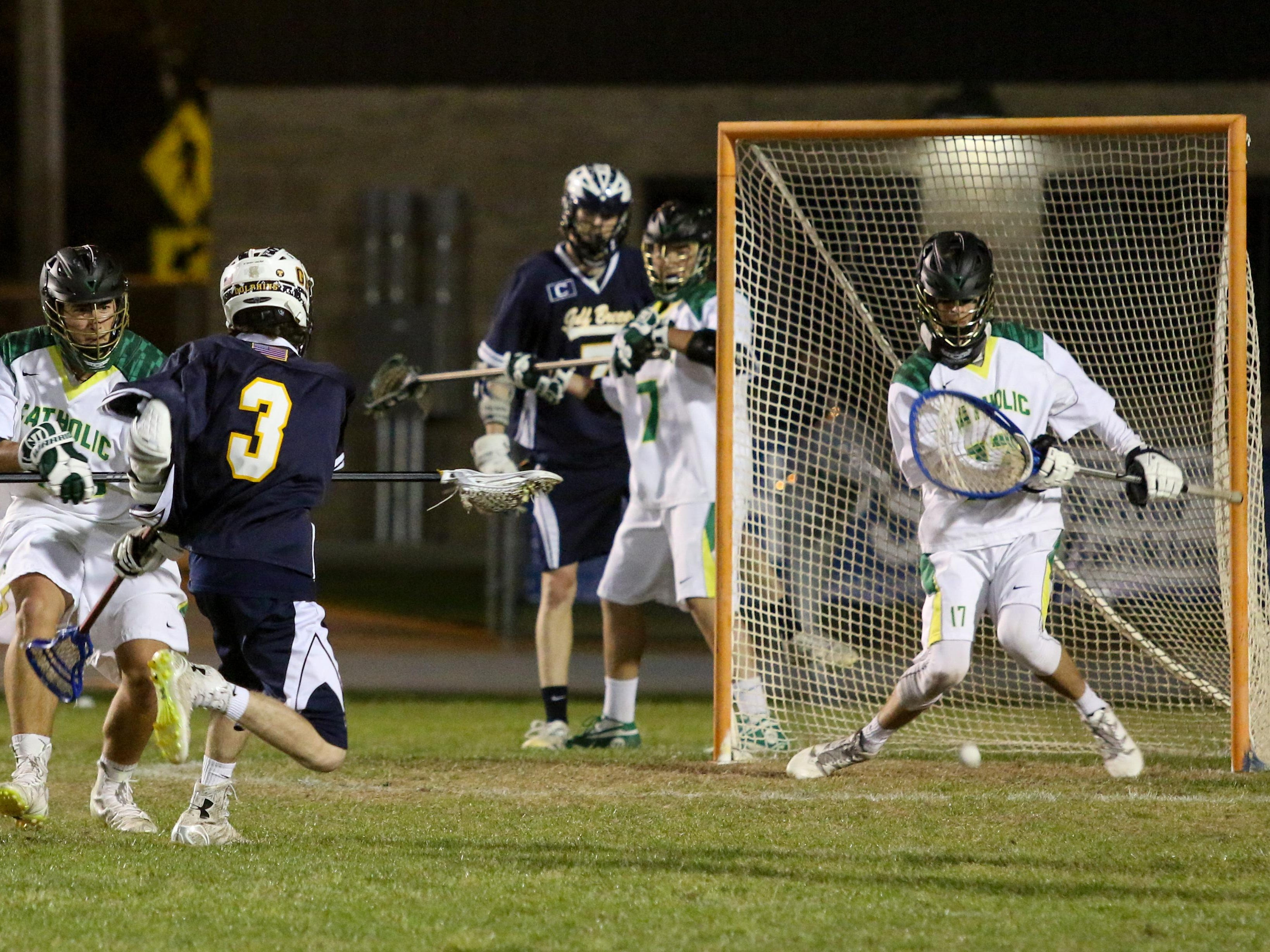 Gulf Breeze's Nick Frazier (3) gets the ball past Catholic's Jack Bartkowski for a goal Friday night during the District 1-1A boys lacrosse championship game at Gulf Breeze High School.