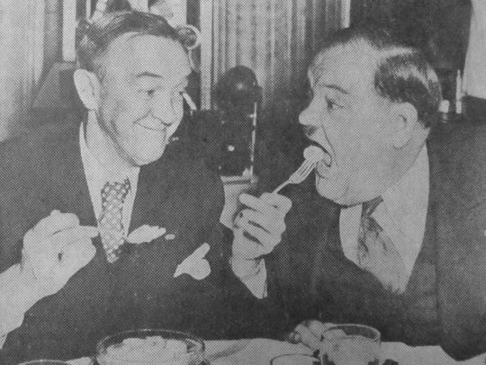 Comedian Stan Laurel feeds a sliced banana to his partner,