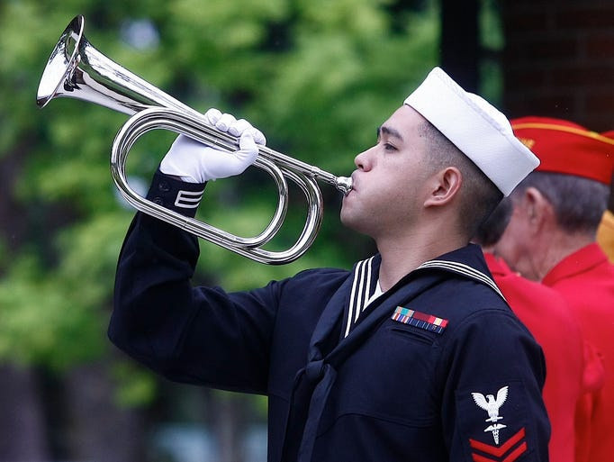 U.S. Marine bugler Stephen K. Palad, a member of a military honor guard from the Engineer Services Company in Springfield, Ore., performs Taps during a memorial service for Joseph Raymond Giesel on Monday, July 21, 2014 at the Roseburg National Cemetery Annex in Roseburg, Ore.