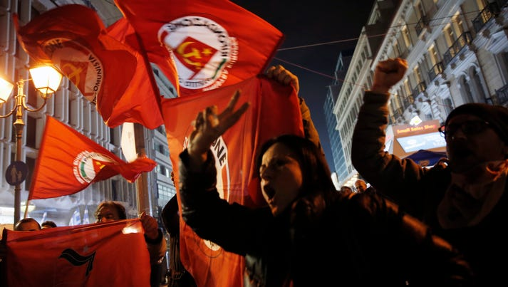 Supporters of left-wing Syriza party react after exit