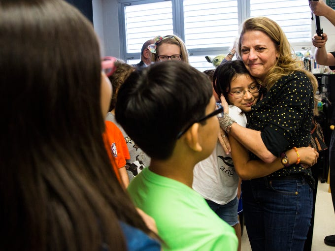 Hope Cliff hugs one of her fifth-grade students after