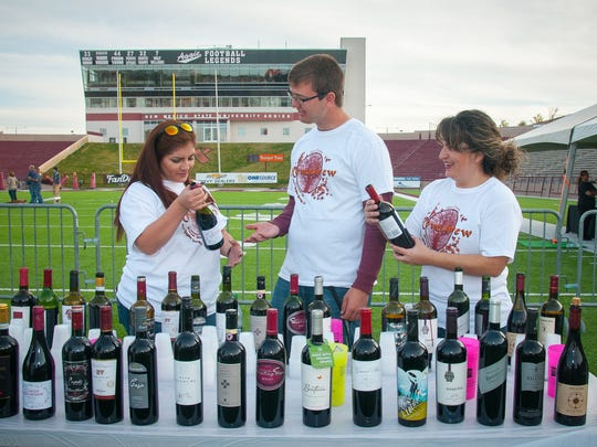 NMSU School of Hotel, Restaurant and Tourism Management students Alex Yebra, left, Austin Keyser and Carla Anaya examine the wines they're offering during the annual beer and wine festival Novembrew at Aggie Memorial Stadium.