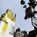 """FILE- In this Aug. 30, 2015 file photo, sign painters work on a portrait of Pope Francis on the side of a New York City office building as some surveillance cameras operated by the New York City Police Department can be seen on lamp posts at either side. New York Police Commissioner William Bratton says local, state and federal law enforcement face an """"unprecedented challenge,"""" ensuring the pontiff's safety as he address over 160 heads of state at the United Nations, presides over a 9/11 memorial service, rides through Central Park and celebrates Mass at Madison Square Garden. (AP Photo/Mark Lennihan, File)"""