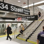 Travelers walk to the No. 7 subway line at the 34th Street and 11th Avenue station in New York City.