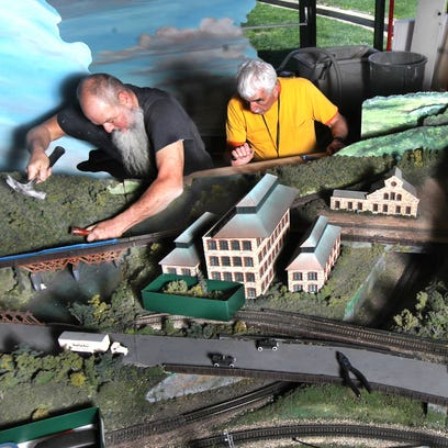 Mark Kohlas (left) and Raymond Devine work to separate two sections of the model train display at the Cincinnati Museum Center.