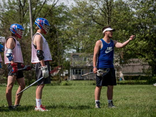 Coach Spencer Macek instructs players during lacrosse practice Wednesday, May 17, 2017 at Eddy Elementary School in St. Clair.