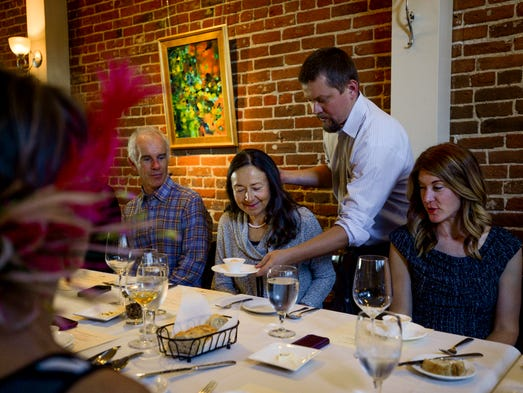 James Gurley serves a dish to Pennie Gerard at a dinner hosted by Chimney Park and NVIDIA Corporation Thursday, May 2, 2014 in Windsor, CO. The proceeds from the dinner benefited the Food Bank for Larimer County and the Weld Food Bank.
