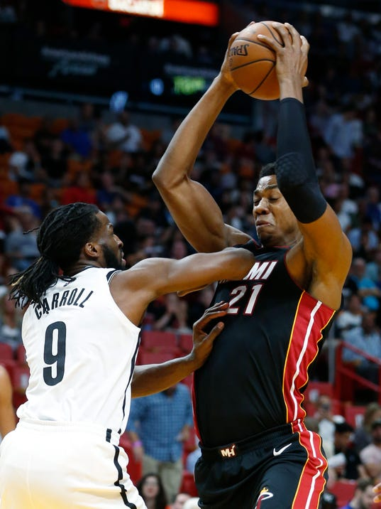 Miami Heat center Hassan Whiteside (21) drives up against Brooklyn Nets forward DeMarre Carroll (9) during the first half of an NBA basketball game, Saturday, March 31, 2018, in Miami. (AP Photo/Wilfredo Lee)