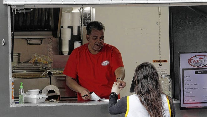 Kawn Howard with the Taesty's food truck takes an order from Emily Roth during a March stop in Upper Arlington. Food trucks are not permitted to set up shop in Delaware's residential areas -- a rule that has frustrated some residents, food-truck owners and the Central Ohio Food Truck Association.
