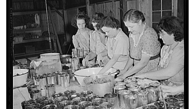 Women preparing cans to be heated and cooked in June of 1943 at the Jefferson County, Kentucky, community cannery. Women paid three cents each for cans and two cents per can for use of the pressure cooker.