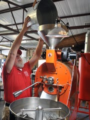 Bill Weske loads a batch of coffee beans into a roaster