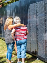 """Visitors to """"The Wall That Heals"""" in Wamego, Kansas. The replica of the Vietnam Veterans Memorial and accompanying mobile education center arrives in Howell on Aug. 21 and will remain through Aug. 26 as part of a national tour."""