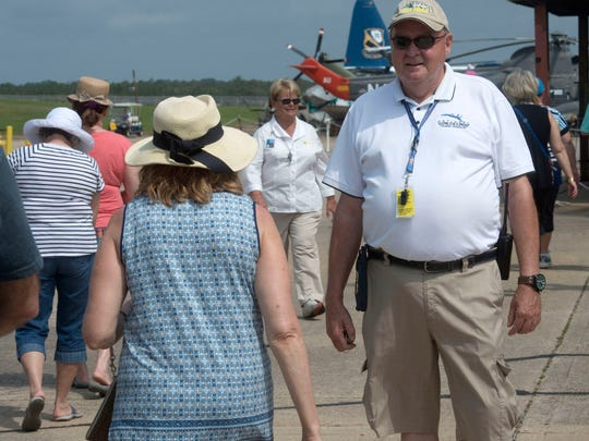 Mike Forrester, a volunteer at National Naval Aviation Museum welcomes and counts the spectators arriving at museum's flight line to watch the Blue Angels practice Tuesday morning April 27, 2016.
