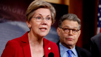 Sen. Elizabeth Warren, D-Mass, left, speaks at a news conference on Capitol Hill in Washington on March 25,2015.  Sen. Al Franken, D-Minn. is at right.