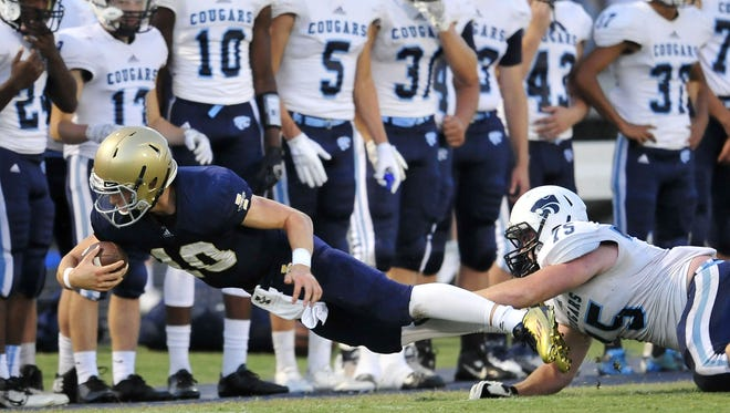 Independence quarterback Andrew Bunch (10) dives for extra yardage after being tackled by Centennial's Grey Drewery.