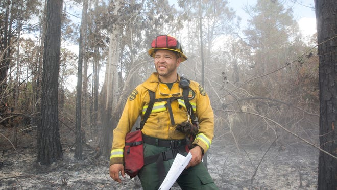 Elmer Sauceda, a wildland firefighter with the Florida Forest Service, stands near the brush fire's point of origin Thursday, March 9, 2017, inside the Picayune Strand State Forest.
