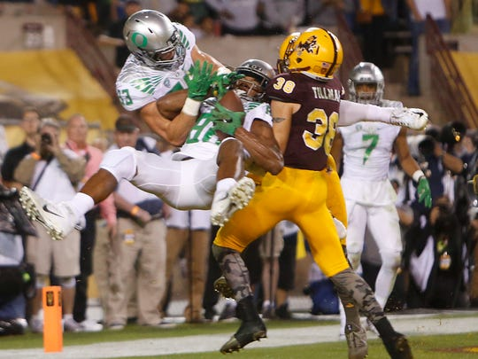 Oregon's Dwayne Stanford (88) makes a catch while colliding with teammate Johnny Mundt (83) in the end zone over Arizona State's Jordan Simone (38) to tie the game with 12 seconds left in the fourth quarter at Sun Devil Stadium in Tempe on Oct. 30, 2015.