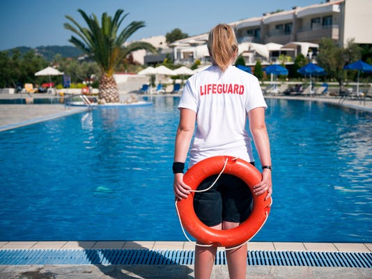A life guard standing by the pool
