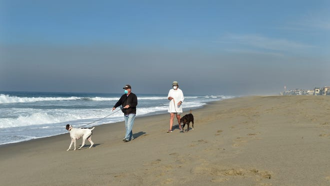 Jim and Jackie Baron walk their two dogs, Rusty and Casey, near their Oxnard Shores home on Thursday. Wearing a mask can ward off some of the health risks brought about by the Thomas Fire, and getting exercise can help relieve holiday stress, health officials say.