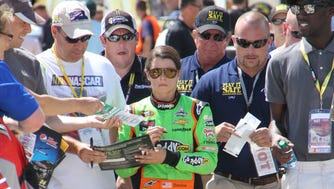 Fans crowd in upon Danica Patrick for signatures.