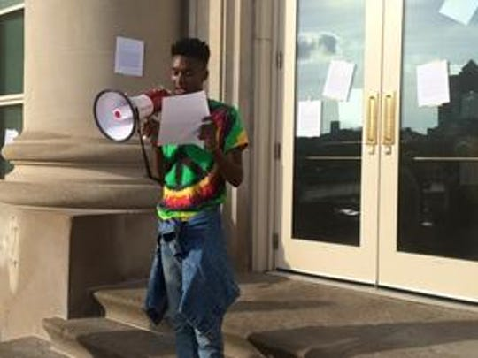 """Avery Jackson, 20, of Des Moines in June reads a letter at a protest outside the Des Moines Police Station. The letter protested """"unlawful police profiling and criminalization of black women, men, and children."""""""